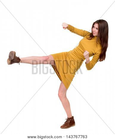 skinny woman funny fights waving his arms and legs. Isolated over white background. Long-haired brunette in a mustard-colored leg raised high.