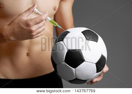 Sportsman injecting ball with steroids on grey background