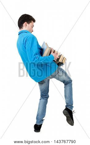 A man carries a heavy pile of books. back view. Rear view people collection.  backside view of person.  Isolated over white background. The curly-haired student in a blue warm sweater tries to hold a