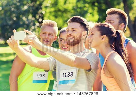 fitness, sport, friendship, technology and healthy lifestyle concept - group of happy sportsmen friends with racing badge numbers taking selfie smartphone outdoors