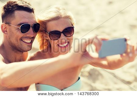 love, travel, tourism, technology and people concept - smiling couple on vacation in swimwear and sunglasses and taking selfie with smartphone on summer beach