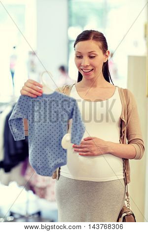 pregnancy, people, sale and expectation concept - happy pregnant woman shopping and buying baby bodysuit at children clothing store