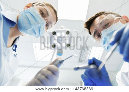 people, medicine, stomatology and health care concept - close up of dentist and assistant with dental mirror, drill and air water gun spray treating patient teeth at dental clinic