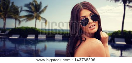 summer vacation, tourism, travel, holidays and people concept -face of young woman with sunglasses over resort beach with palms and swimming pool background