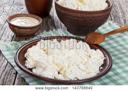 cottage cheese on clay dish with wooden spoon on kitchen tablecloth sour cream in a small bowl on the old rustic boards view from above close-up