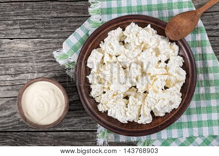 cottage cheese on clay dish with wooden spoon on kitchen tablecloth sour cream in a small bowl on the old rustic boards top view