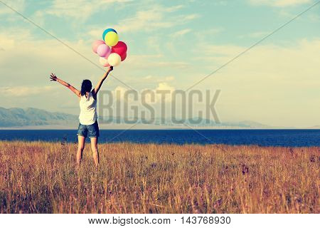 young woman with colorful balloons on grassland
