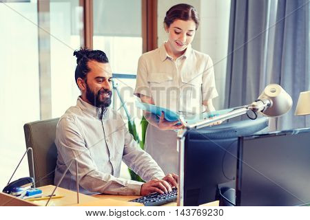 business, startup and people concept - happy creative team with computer and files in office