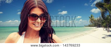summer vacation, tourism, travel, holidays and people concept - face of smiling young woman with sunglasses over tropical beach with palms background