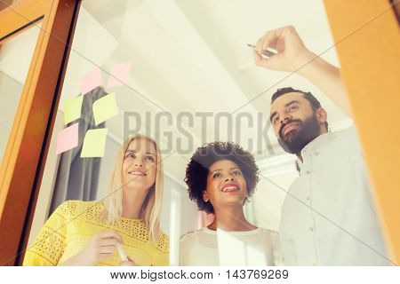 business, startup, planning, management and people concept - happy international creative team writing on stickers at office glass board