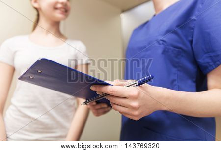 medicine, health care and people concept - close up of female doctor or nurse holding clipboard with pen and talking to girl at hospital