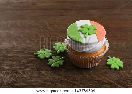 Tasty cupcake with clover on wooden background. Saint Patrics Day concept