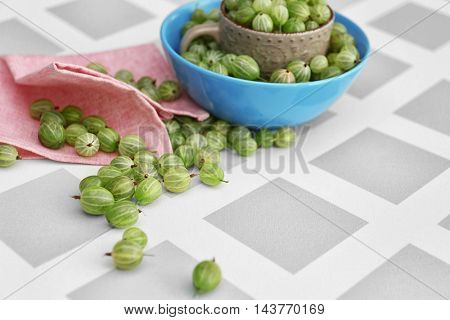 Gooseberries with cup and bowl on table