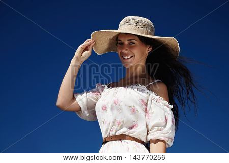 woman's outdoor portrait in summer hat on the sky background
