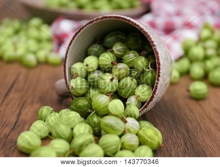 Gooseberries with cup on table