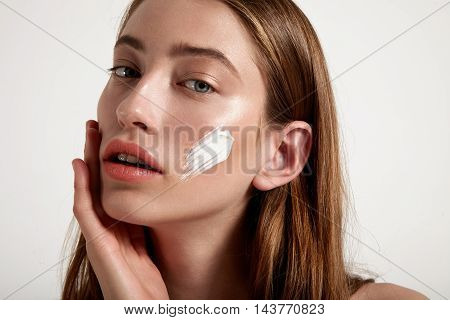 fashioon model with cream on cheek and blue eyes