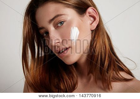 young model with cream on cheek and blue eyes