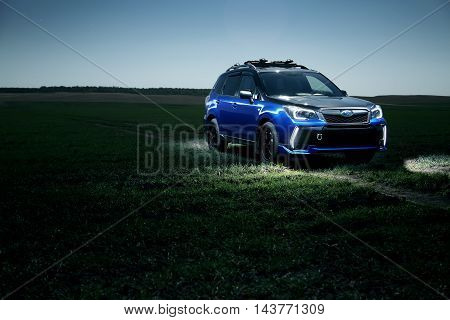 Saratov, Russia - September 28, 2015: Car Subaru Forester stand at countryside off-road on green field at night