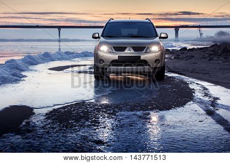 Saratov, Russia - November 27, 2014: Car Mitsubishi Outlander stay on ice coast at winter sunset