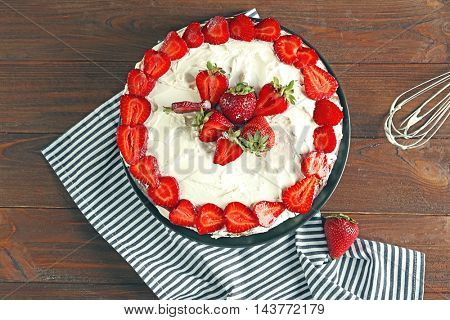 Appetizing cake decorated with strawberry on wooden table