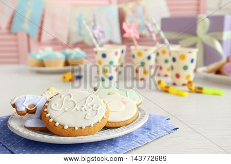 Baby glazed cookies in plate on decorated table