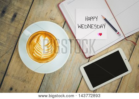 Happy Wednesday on paper with coffee cup on wood background