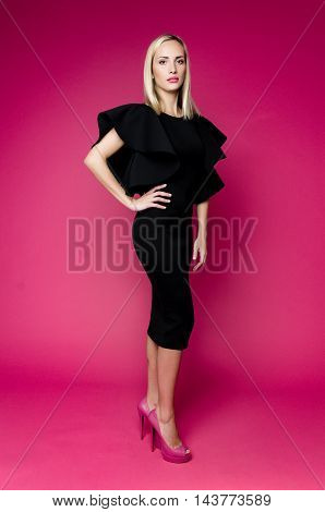 Female portrait of cute lady in studio wearing black dress. Close up beautiful sexy model girl in elegant pose. Closeup beauty blonde woman with hairstyle on pink background