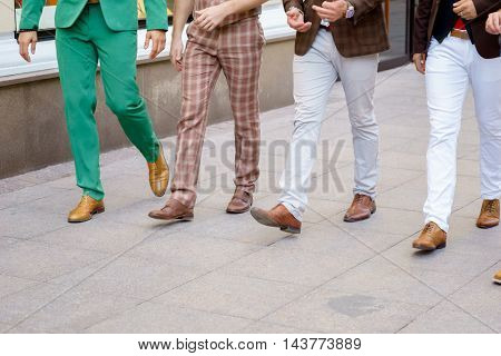 Group of stylish men walking down the street