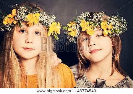 two Young Smiling Girls Sisters with flowers