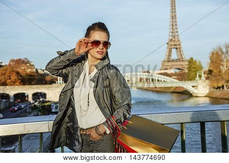 Elegant Woman With Shopping Bags Looking Aside Near Eiffel Tower