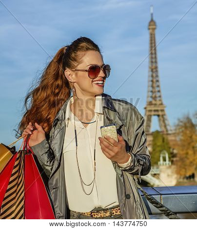 Woman With Shopping Bags And Smartphone In Paris Looking Aside