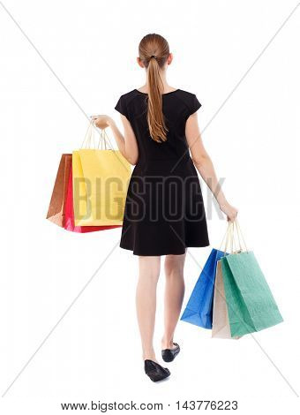 back view of going  woman  with shopping bags . beautiful girl in motion.  backside view of person.  Rear view people collection. Isolated over white background. Blonde in a short black dress shopping