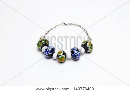 Bracelet with colored glass beads on white background
