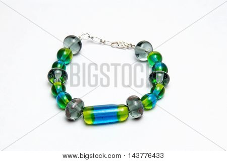 Bracelet with green and blue glass beads on white background
