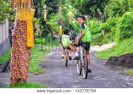 Bali,Indonesia - May 29, 2010 : Balinese kids enjoying ride bicycle on village road at Bali,Indonesia on 29th May 2010.