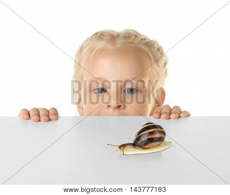 Funny little girl hiding behind white table and looking at snail