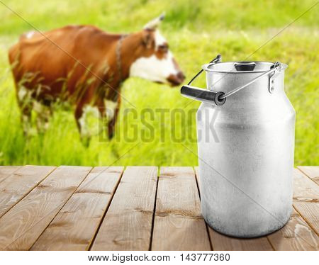 Retro can for milk on wooden table. Cow on pasture, blurred background.