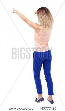 Back view of  pointing woman. beautiful girl. Rear view people collection.  backside view of person.  Isolated over white background. Blonde in blue pants I saw something in the distance.
