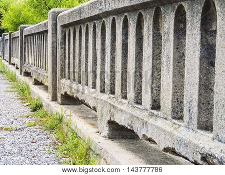 Old concrete bridge railing with overgrown grass along the base