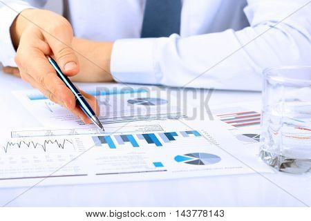 Close-up Of Businessman Analyzing Graphs with pen