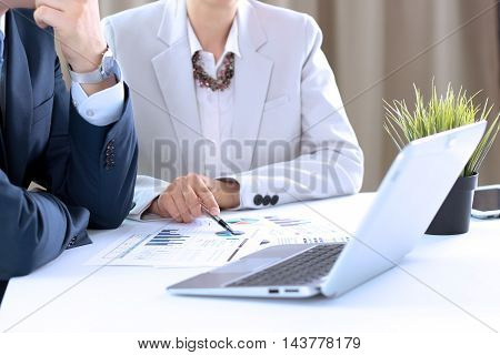 Business colleagues working and analyzing financial figures on a digital laptop