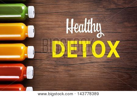 Bottles with delicious detox drinks and text healthy detox on wooden background. Detox diet concept.