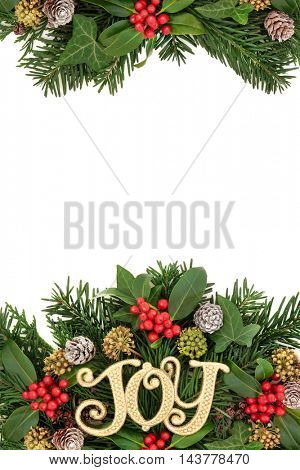 Christmas border with joy sign decoration, flora of holly and berries, ivy, snow covered pine cones, cedar cypress and fir leaf sprigs over white background.