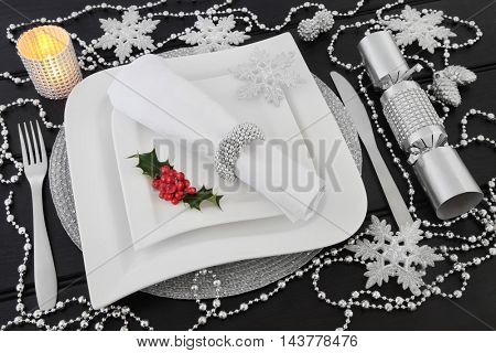 Christmas dinner table setting with white porcelain plates, holly, silver bead decorations, candle, cutlery, linen napkin with ring and cracker over dark wood background.