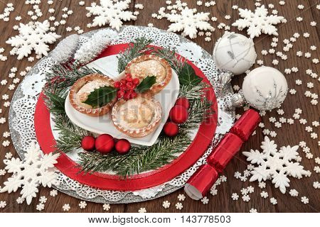 Christmas mince pie cakes with holly, red and white bauble decorations with winter greenery and  snowflakes over oak background.