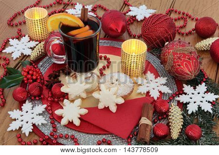Christmas still life scene with snowflake gingerbread biscuits and decorations, mulled wine, mince pie, baubles, candles, orange fruit and spices, holly and snow covered fir on oak background.
