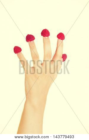 Hand with raspberries.