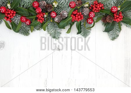 Fantasy christmas background border with fly agaric mushroom decorations, holly, ivy, mistletoe, snow covered  fir and pine cones over distressed white wood.