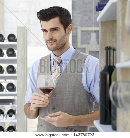 Elegant young man holding glass of red wine, looking away.