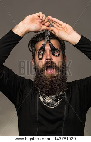 young handsome bearded man with long beard moustache and brunette hair holding hairdresser or barber scissors with emotional face in studio on grey background